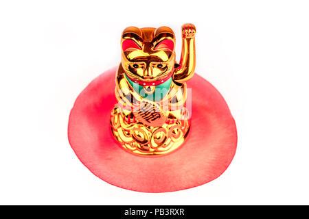 Maneki neko, Japanese lucky beckoning cat figurine, on white with the flag of Japan - Stock Photo
