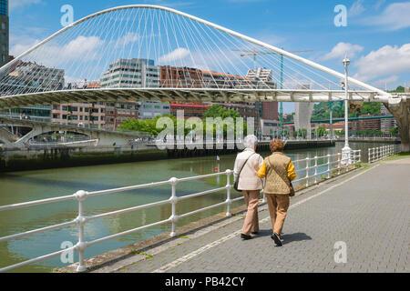 Women friends, rear view of two well-dressed mature women walking alongside the River de Bilbao in Bilbao, Northern Spain. - Stock Photo