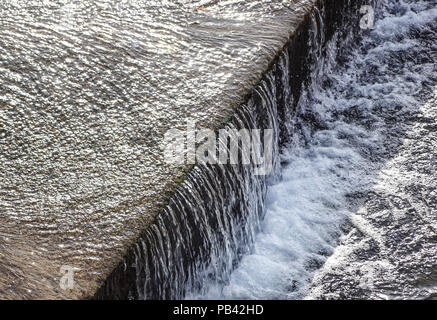 Regulated water flow of and irrigation channel that flows through the middle of a city.