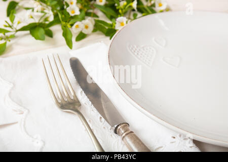 Holiday dinner. Table place setting with empty plates, silver fork and knife, closeup view - Stock Photo