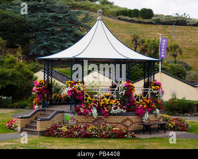 Summer bedding flowers bedeck the Victorian bandstand in Runnymede Gardens, Ilfracombe, Devon, UK - Stock Photo
