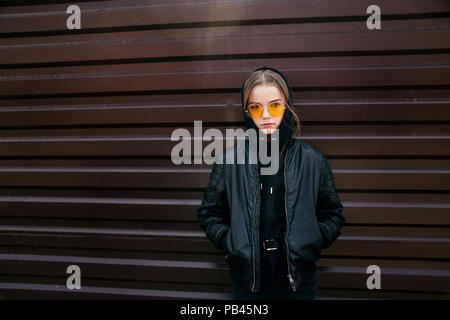 Fashion kid concept - stylish little girl child wearing black casual clothes and sunglasses posing summer in the city - Stock Photo