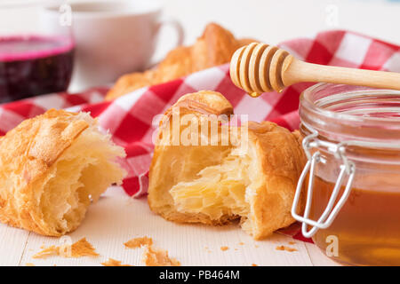French style breakfast, a white wooden table with glass of fresh beetroot smoothie, croissants and glass bowl of honey, few croissants placed on the r - Stock Photo