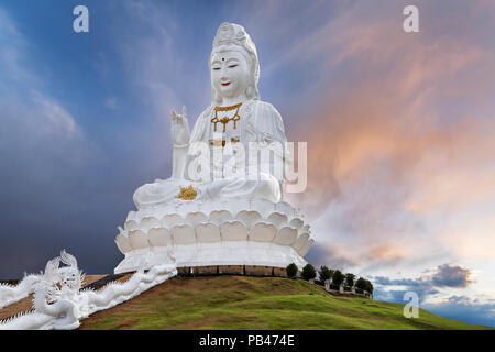 Big Guan Yin Statue representing goddess of compassion and mercy, at the sunset, in Chiang Rai, Thailand. - Stock Photo