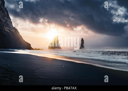 Sunrise at famous Black Sand Beach Reynisfjara in Iceland. Windy Morning. Ocean Waves. Colorful Sky. Morning Sunset. - Stock Photo