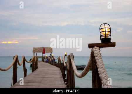 Wooden bridge in to the sea evening time - Stock Photo