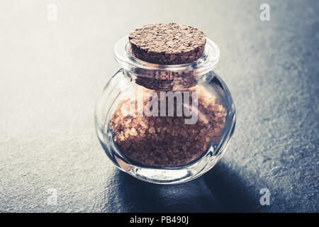 Close-Up Of A Brown Raw Sugar In A Small Glass Bottle Closed With A Cork Stopper On Slate Stone - Stock Photo