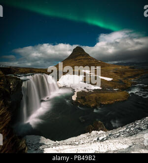 Northern lights aurora borealis appear over Mount Kirkjufell in Iceland. - Stock Photo