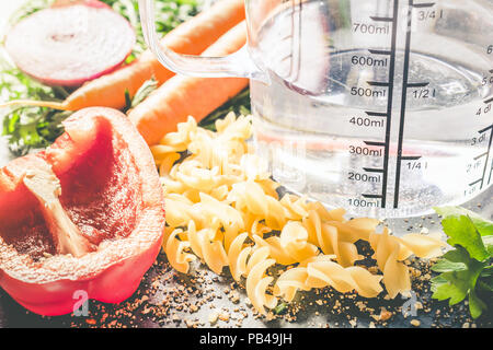 400 ml - ccm Water In A Measuring Cup Surrounded By Noodles, Pepper, Onion, Carrots And Spices - Stock Photo