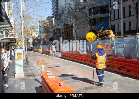 Female traffic controller manages traffic along George street in Sydney during construction of the light rail project,Sydney,Australia - Stock Photo