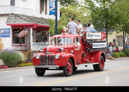 Frankenmuth, Michigan, USA - June 10, 2018 Men riding on the back of a classic firetruck playing music instruments going down the road at the Bavarian - Stock Photo