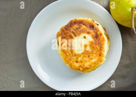 Stack of Homemade Scrumptious Mascarpone Pancakes Patties on White Plate Dark Grey Cotton Napkin. Pear. Rustic Provence Style Kitchen Interior. Mornin - Stock Photo
