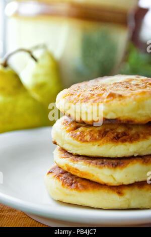 Stack of Homemade Scrumptious Mascarpone Pancakes Patties on White Plate Dark Grey Cotton Napkin. Pear. Rustic Kitchen Interior. Morning Breakfast. Co - Stock Photo