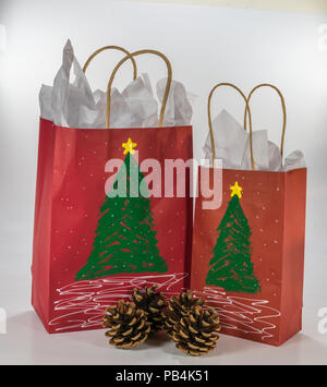 Two red gift bags decorated for Christmas and ready for giving along with four pine cones - Stock Photo
