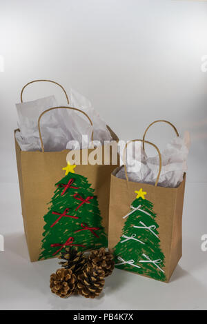 Two paper gift bags decorated for Christmas and ready for giving along with four pine cones - Stock Photo