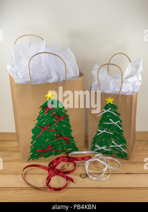 Two paper gift bags decorated for Christmas and ready for giving along with red and white ribbon - Stock Photo
