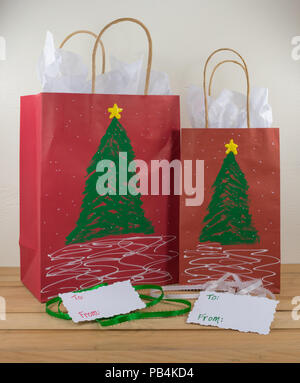 Two red paper gift bags decorated for Christmas and ready for giving along with tags and green and white ribbon - Stock Photo