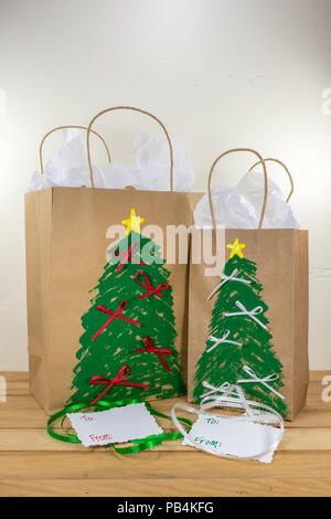 Two paper gift bags decorated for Christmas and ready for giving along with tags and green  and white ribbon - Stock Photo