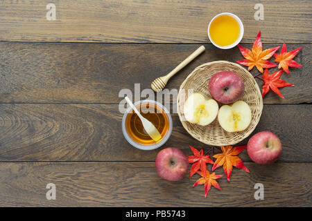 Table top view aerial image of decoration Fall harvest or Rosh Hashanah day background concept.Flat lay apple slice & honey bee with maple leave on mo - Stock Photo