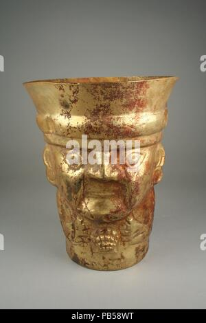 Beaker, Figure with Shell. Culture: Lambayeque (Sicán). Dimensions: H. 10 x Diam. 8 in. (25.4 x 20.3 cm). Date: 9th-11th century.  Gold beakers, both plain and ornamented with embossed designs, were markers of status and authority on Peru's north coast in the centuries before the rise of the Inca Empire. This vessel was sculpted in the shape of the torso and head of an individual wearing a cap and holding a shell. One side of the beaker features the embossed face and hands, while the other side is rendered as the back of the individual's head. The figure wears round ear ornaments, and the hair - Stock Photo