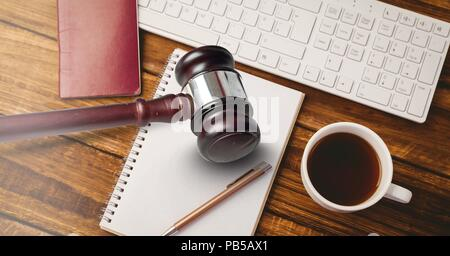 Gavel and keyboard with notepads and coffee on desk - Stock Photo