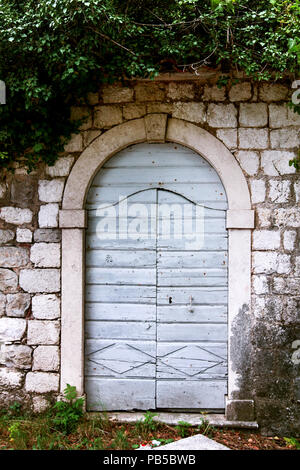 Old door and window on a stone wall Mediterranean house in Montenegro - Stock Photo