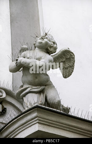 Statue of a child angel in the exterior niche of St Michael 18th century church in Budapest, Hungary - Stock Photo