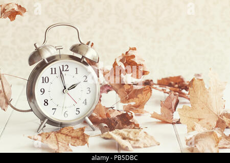 Faded Alarm clock in colorful autumn leaves against a retro background with shallow depth of field. Daylight savings time concept. - Stock Photo