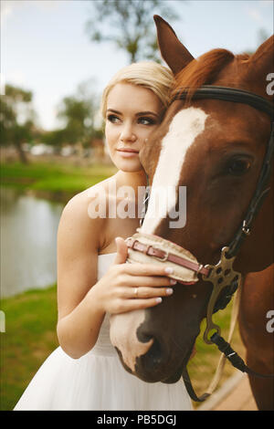 Beautiful and fashionable blonde model girl with blue eyes, with stylish hairstyle and bright makeup, in white dress posing with brown horse outdoors - Stock Photo