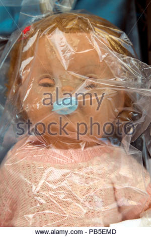 doll in clear plastic bag - Stock Photo