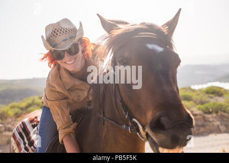beautiful cheerful young woman enjoy and ride her brown cute horse in friendship and relationship. animal lover and pet therapy concept. travel and va - Stock Photo