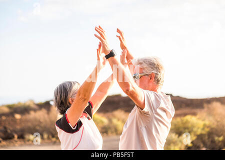 senior mature couple enjoy and win together giving five and hugging under a nice weather day of sun in summer. sport activity and clothes. Active aged - Stock Photo
