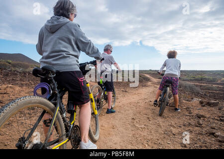 group of ciclyst with mountina bikes riding on the desert in tropical island and enjoying the leisure outdoor sport activty to stay health and nice. b - Stock Photo