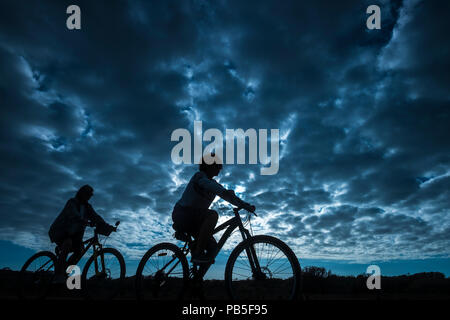 couple of rider in mountain bike come back home after a sport bikes session outdoor. beautiful blue sky with clouds in backgorund. people in silhouett - Stock Photo