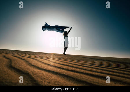 beautiful thin body woman enjoy freedom and summer travel laying with the wind in the desert sand. beach and vacation concept for freedom and joyful l