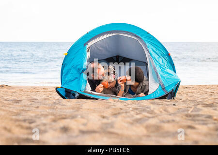 couple looking at the smart phone and have fun inside a tent in free camping on the beach Dog border collie behind them looking at the camera. vintage - Stock Photo
