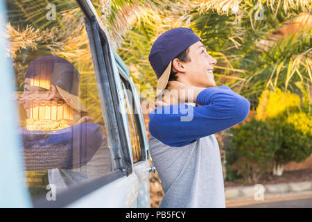 beautiful male teenager in casual dress outdoor in leisure activity smiling and enjoying the tropical weather. mirrored in a vintage van vehicle