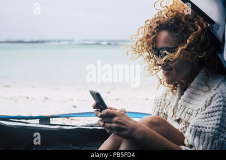 cheerful traveler lady with curly hair in the wind write on smartphone enjoyng the tent outdoor at the beach. ocean in background. paradise vacation c - Stock Photo