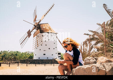 nice beautiful cheerful lady with blonde curly hair sitting under a windmill in outdoor scenic place reading a book and enjoying the leisure activity. - Stock Photo