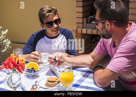 family daily happy scene with father and son caucasian people having breakfast together in the morning, summer sun for happy couple of young and old m - Stock Photo