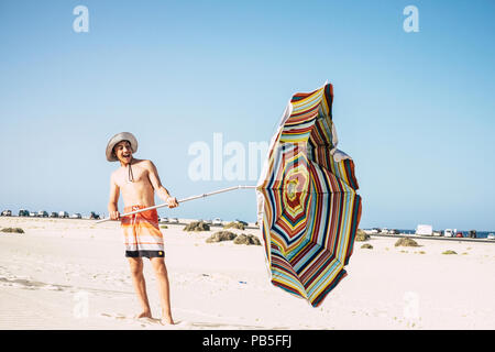 young male caucasian teenager play with umbrella sun and wind in a sandy paradise beach. smile and have fun enjoying the holiday and the warm weather  - Stock Photo