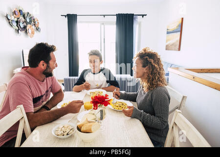 happy and cheerful caucasian family having lunch together at home. white wall and bright image. together enjoy the day smiling and looking with love a - Stock Photo