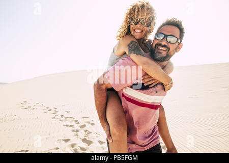 people and couple in love have fun and enjoy the desert dunes at the beach on vacation. man carry on his back the beautiful curly hair woman smiling a - Stock Photo
