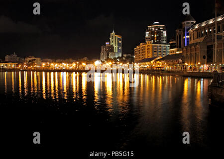Caudan Waterfront and urban skyline of Port Louis, Mauritius, reflecting in the water at night - Stock Photo
