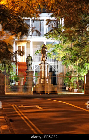 Entrance gate of the Government House with the bronze statue of the British Queen Victoria in the court of honour - Port Louis, Mauritius - Stock Photo