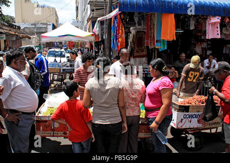 People buying at the street market outside the official market halls in Port Louis - Stock Photo