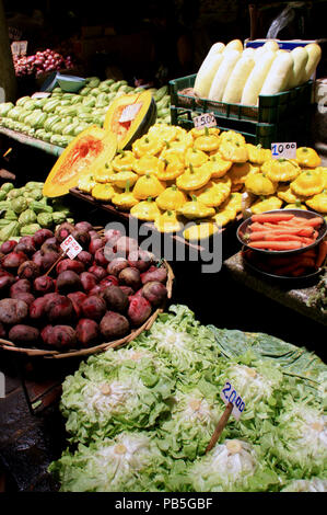 Pumpkins, carrots and beets for sale at a stall in the fruits and vegetables market hall in Port Louis - Stock Photo