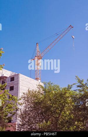 Tower construction site with crane and buildings with blue sky background - Stock Photo