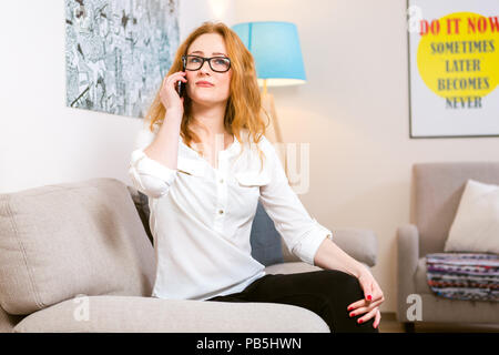 Business woman theme. Beautiful young woman with long curly red hair uses a mobile phone, calls and speaks sitting on the sofa in the house. Dressed i - Stock Photo