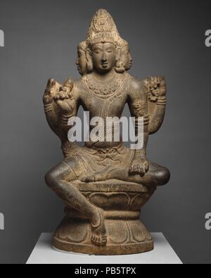 Shiva as Mahesha. Culture: India (Tamil Nadu). Dimensions: H. 58 in. (147.3 cm); W. 32 in. (81.3 cm); D. 16 in. (40.6 cm). Date: 10th century.  This statue is part of a group of unusual large stone carvings in the round from the Chola period. They all portray the same deity, long identified as Brahma but now thought to be Mahesha, a form of Shiva. Shiva's worshipers believe that he manifests himself in three stages, which move from the abstract to the concrete--symbolized by the undecorated linga (shaft); the linga with one or more faces emerging from it; and, finally, Mahesha. From him are bo - Stock Photo